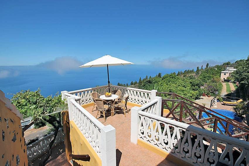 Pequeña terraza con muebles de jardín y vistas al mar