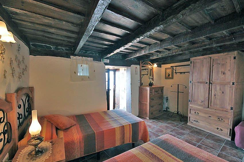 Dormitorio rústico con techo de madera